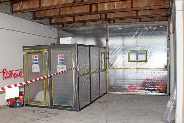 View of the asbestos enclosure inside a small shop unit with 3-stage airlock and baglocks set up