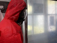 Remove  Asbestos operative entering an enclosure wearing red overalls and RPE