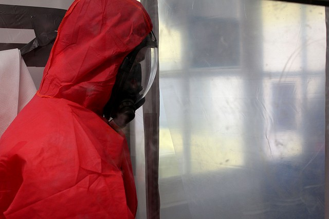 Asbestos operative entering an enclosure with full RPE and overalls